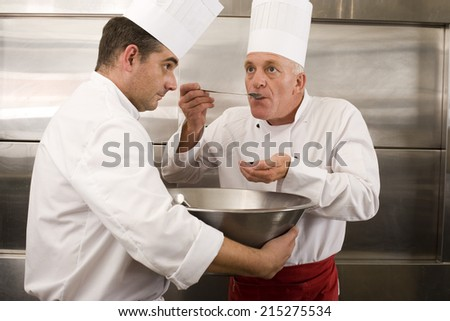 Chef holding large bowl in commercial kitchen, second chef tasting food sample with large spoon - stock photo