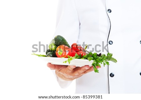 chef holding plate with fresh vegetables