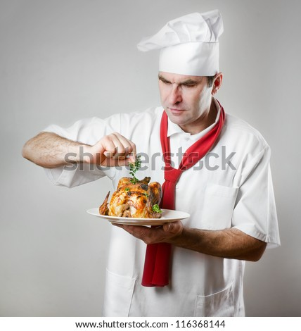Chef holding plate with roasted chicken - stock photo