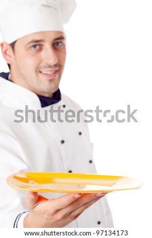Chef holding plate with something. Focused on plate. Isolated over white.
