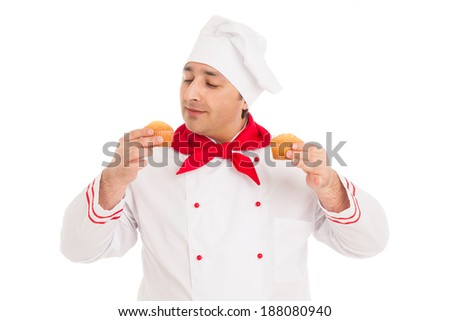 chef holding two muffins wearing red and white uniform over white background