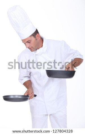 Chef holding two saucepans - stock photo