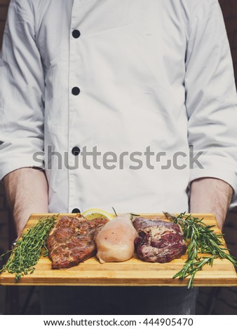 Chef holds fresh steaks ready for BBQ cooking - pork, beef and chicken. Raw meat on a cutting board with rosemary leaf on wood, closeup. Marinated in spices for barbecue. - stock photo