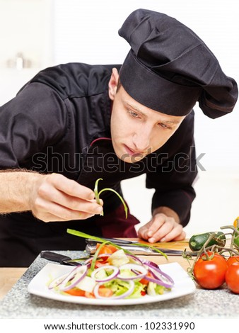 chef in black uniform decorating delicious salad plate - stock photo