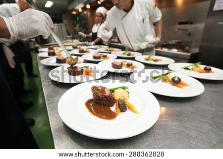 Chef in hotel or restaurant kitchen cooking for dinner - stock photo