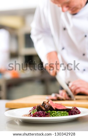 Chef in hotel or restaurant kitchen cooking, he is cutting meat or steak for a dish on plate - stock photo