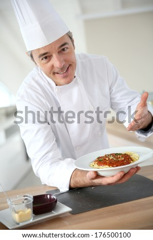Chef in kitchen presenting italian dish  - stock photo