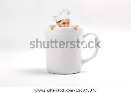 Chef In Uniform Sitting In White Mug On White Background - stock photo