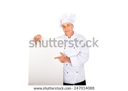 Chef in white uniform holding empty banner. - stock photo