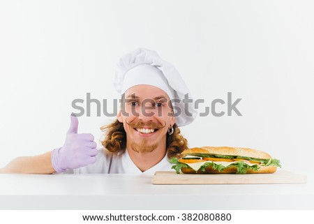 Chef in white uniform show big finger up and smile, vegetarian sandwich laying on the table in front of him. Conception of healthy food and healthy lifestyle. Cooking vegetarian sandwich