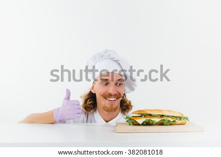 Chef in white uniform show big finger up, smile and watch on vegetarian sandwich laying on the table in front of him. Conception of healthy food and healthy lifestyle. Cooking vegetarian sandwich