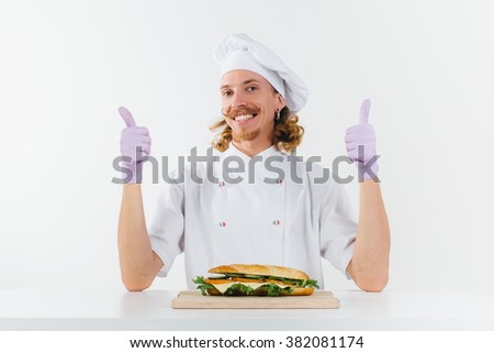 Chef in white uniform show big fingers up and smile, vegetable sandwich lays on the table in front of him. Conception of healthy food and healthy lifestyle. Cooking vegetarian sandwich