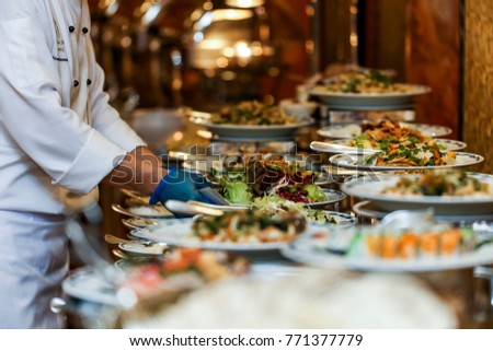 Chef arranging food on buffet table stock photo royalty free chef is arranging the food on buffet table watchthetrailerfo
