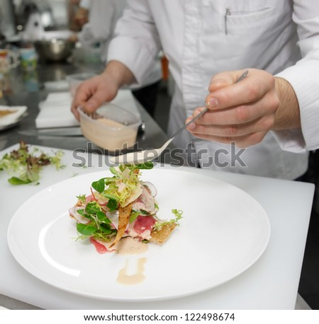 Chef is cooking fish appetizer on professional kitchen - stock photo