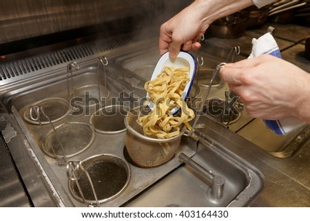 Chef is cooking pasta at commercial kitchen - stock photo