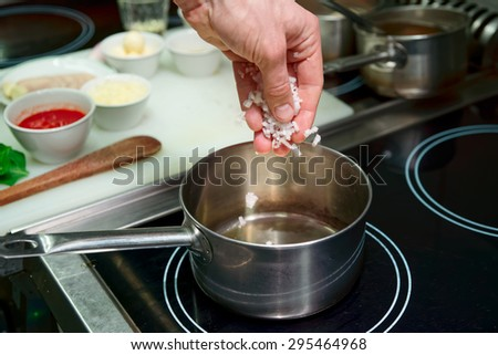 Chef is frying onion to make risotto, commercial kitchen - stock photo