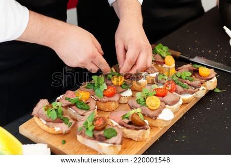 Chef is making bruschettas with beefsteak and pesto sauce - stock photo
