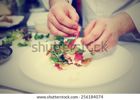 Chef is making fish appetizer on restaurant kitchen, toned image - stock photo