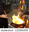 Chef is making flambe dish on restaurant kitchen - stock photo