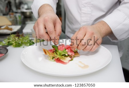 Chef is making seafood appetizer on professional kitchen - stock photo