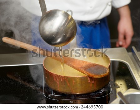 Chef is pouring broth in boiling risotto - stock photo