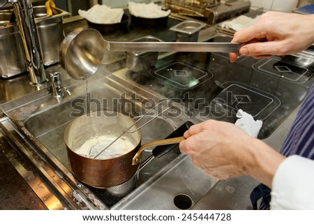 Chef is pouring broth in sauce, commercial kitchen - stock photo