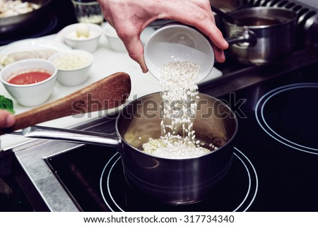 Chef is pouring rice in stewpan, toned image - stock photo