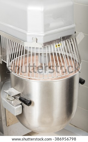 chef is preparing cake mix in industrial bread mixer- kneading machine - stock photo
