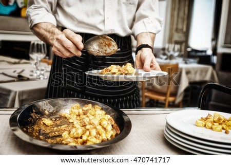 Chef is putting gnocchi with meat in plates, toned image