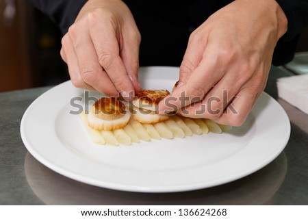 Chef is serving foie gras with grilled scallops - stock photo
