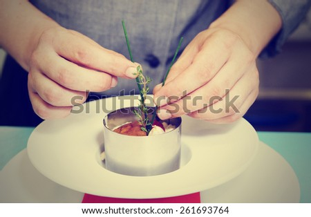 Chef is serving risotto with stainless steel form, toned image - stock photo