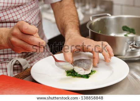 Chef is serving steamed seabass with spinach