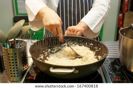Chef is stirring risotto in a large pan, strong motion blur - stock photo