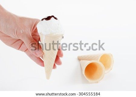 Chef makes the ball ice cream in a cone, waffle cup, watering chocolate - stock photo
