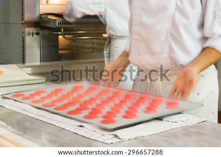 Chef making a pink macaroon (Motion blur for dynamic of action scene look though window glass at open kitchen)