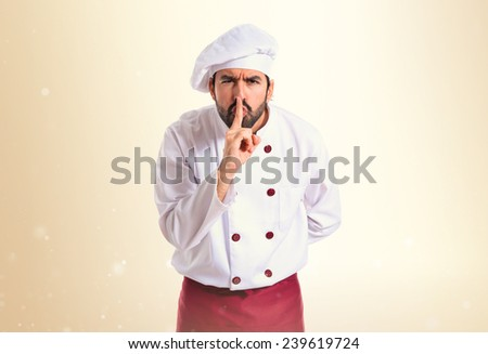 Chef making silence gesture over ocher background - stock photo