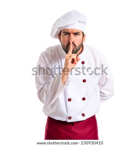 Chef making silence gesture over white background - stock photo