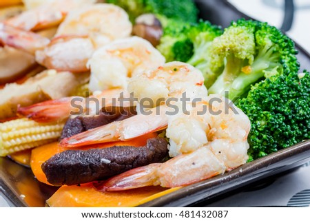 chef making Stir-Fried Broccoli carrot, baby corn with prawns