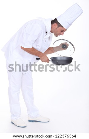 Chef monitoring sauce in pan - stock photo