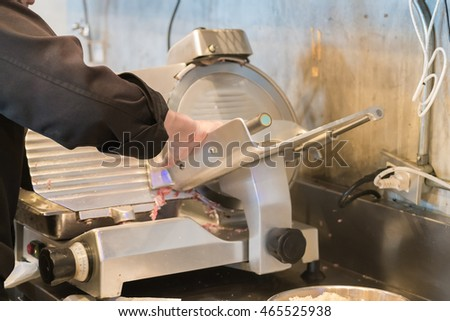 Chef operating meat slicer machine