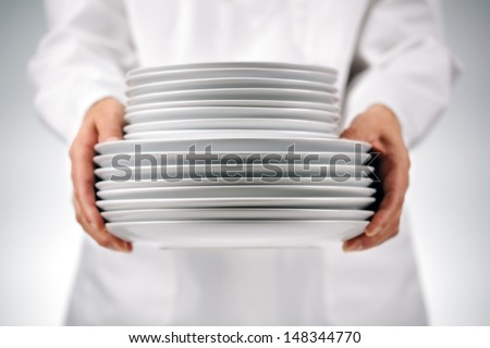 Chef or waitress holding plates in a restaurant kitchen - stock photo