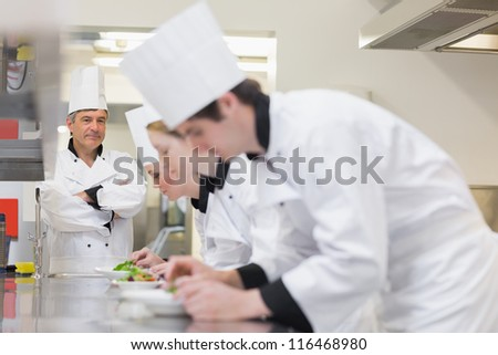 Chef overlooking others preparing salads in kitchen