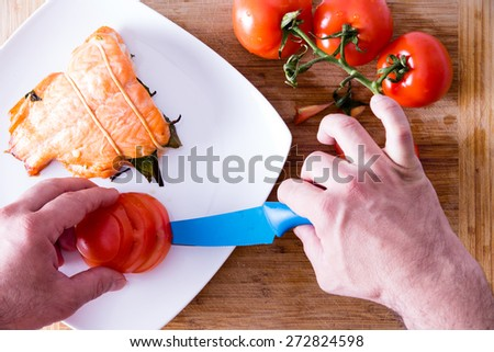 Chef plating up a gourmet salmon dinner carefully arranging sliced fresh tomato alongside an oven-baked fish fillet, view from above - stock photo