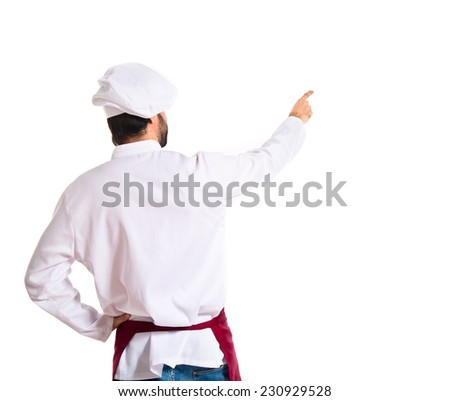 Chef pointing back over white background - stock photo