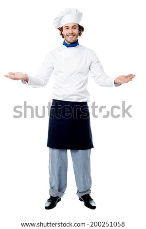 Chef posing with his arms wide open, welcoming guests - stock photo