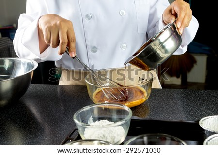chef pouring chocolate into a bowl  to make chocolate cake - stock photo