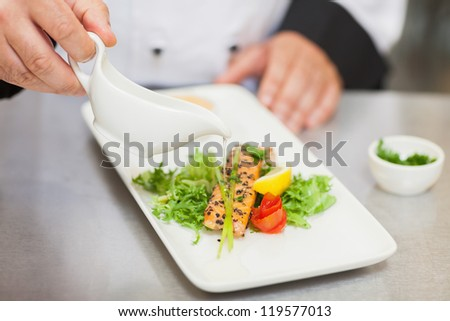 Chef pouring sauce on salmon dish in the kitchen