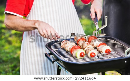 Chef prepares a barbecue on the grill - stock photo