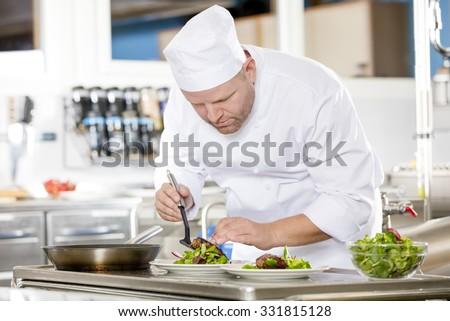 Chef prepares steak dish at gourmet restaurant - stock photo
