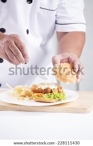 chef preparing a burger on the table